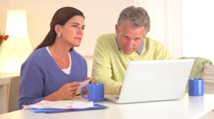 Senior couple paying bills online Stock Footage