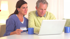 Senior couple buying getaway vacation Stock Footage