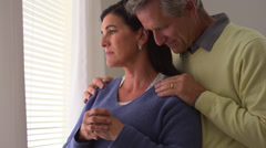 Depressed senior wife standing by window with husband Stock Footage