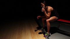 Female Fitness Trainer Resting in Dark Gym - stock footage