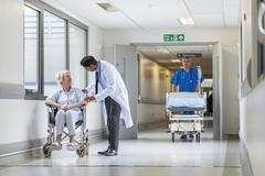 doctor patient hospital corridor nurse pushing gurney stretcher bed - stock photo