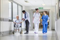 Doctors nurse senior female patient in hospital corridor Stock Photos