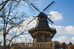 traditional old european windmil at forest scenery against blue sky - stock photo