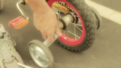 A father puts training wheels on bike Stock Footage