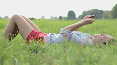 Young woman lying on the grass and sending sms, texting in the park HD Stock Footage