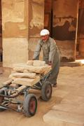 local man working at karnak temple complex, luxor - stock photo