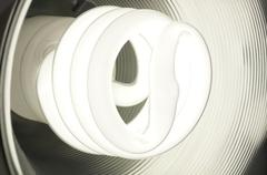 Compact Fluorescent Light Bulb Glowing Stock Photos