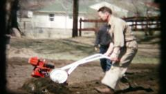 441 - rototiller is used by family members in garden - vintage film home movie Stock Footage