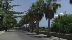 Couple walking on the street with Palm trees and lampions. Stock Footage