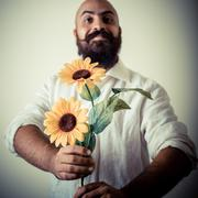 long beard and mustache man giving flowers - stock photo