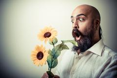 Long beard and mustache man giving flowers Stock Photos