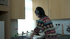 Woman washing up, dancing to music Stock Footage