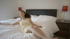 Woman jumps onto bed Stock Footage