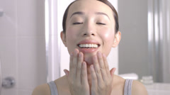 Young Asian woman massaging face Stock Footage