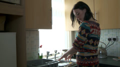 Female washing up, stops to answer phone - stock footage