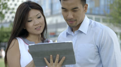 Asian Man and woman looking at digital tablet outdoors Stock Footage