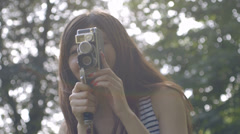Young woman filming with retro camera Stock Footage