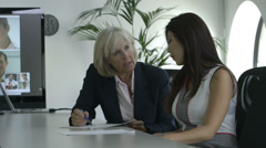 Senior Businesswoman and Asian woman discussing in office - stock footage