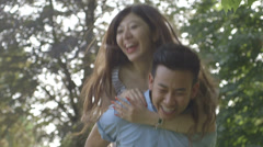 Man giving woman piggyback - stock footage