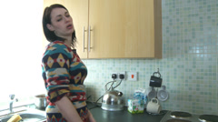Stock Video Footage of Young woman enters kitchen to make tea arguing, angry, upset