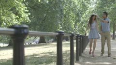 Young Asian tourist couple walking in park Stock Footage
