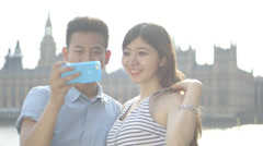 Young Asian tourist couple taking self-portrait Stock Footage