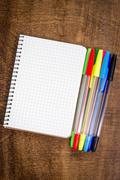 spiral notebook and colorful pens - stock photo