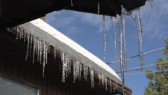 Icicles on roof, rack focus on icicles in bg Stock Footage