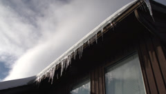 Icicles on roof wide low angle, good sky Stock Footage