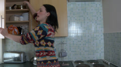 Woman in kitchen cooking in a rush - stock footage