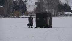 man stands next to fishing hut on frozen lake pondering his next more, long shot - stock footage
