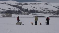 Ice fishermen on frozen lake long shot Stock Footage