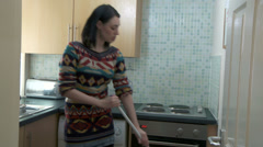Female dancing while doing housework Stock Footage