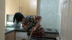 Female in kitchen cleaning in a panic Stock Footage
