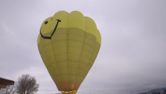 hot air balloon yellow happy face, tilt down to reveal balloon crew... - stock footage