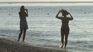 Stock Video Footage of Two young womans taking photos on the beach, silhouettes.