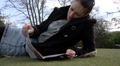 Female lying on grass reading a magazine HD Footage