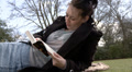 Woman relaxing outside with a book Footage