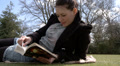 Pretty woman reading a book in the park HD Footage