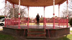 Pretty woman walks away from bandstand - stock footage