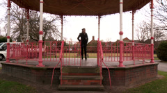 Female walks away from bandstand and answers her phone Stock Footage