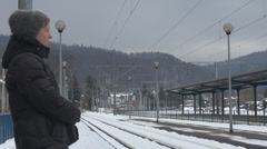 Young woman wait train station winter snow look watch rail girl travel transport Stock Footage