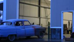 Antique car restoration pulling out of the shop. Stock Footage