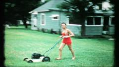 Dad films his daughter cutting the grass in backyard,448 vintage film home movie Stock Footage