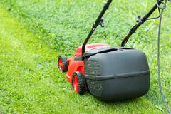 New lawnmower on green grass Stock Photos
