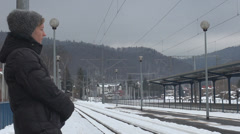 Young woman wait train station winter snow platform rail girl travel transport Stock Footage