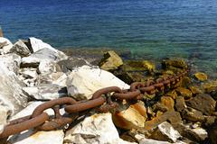 a metal chain secures a distant ship to the shore. - stock photo