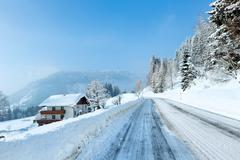 morning winter misty rural alpine road and house - stock photo