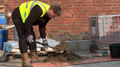 Brick layer mixing cement Stock Footage