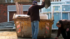 Two old men filling a skip Stock Footage